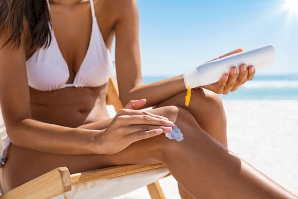 Skin cancer prevention - woman applying sunscreen